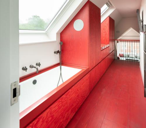 Badezimmer in Rot unter der Schräge viel Tageslicht rote Vertäfelung Badewanne unter dem Dachfenster rote Schränke