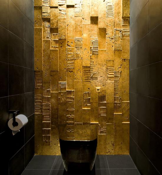 Badezimmer in Schwarz und Gold WC eine Wand in Goldschimmer interessante Oberfläche andere zwei Wände Boden und Toilettenschüssel schwarz