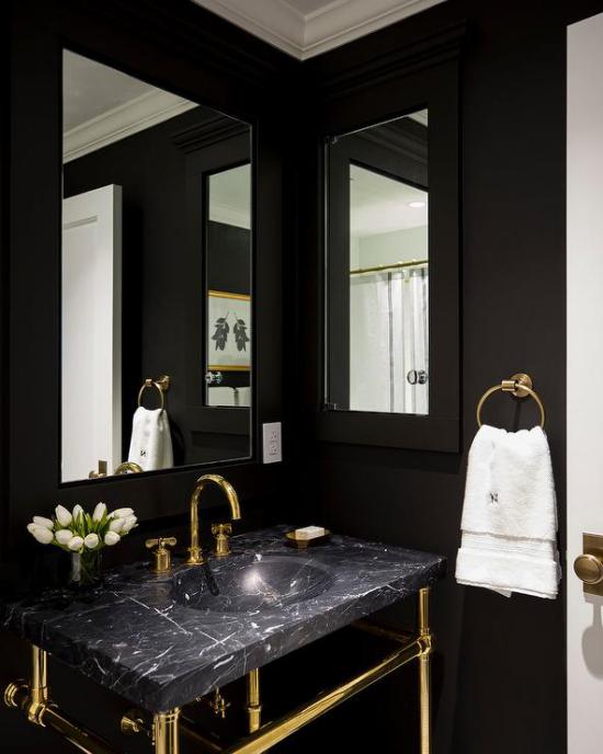 Badezimmer in Schwarz und Gold Waschtisch schwarzer Marmor natürliches Licht zwei Spiegel weiße Tulpen weißes Tuch