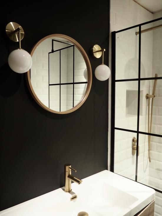 Badezimmer in Schwarz und Gold das Farbschema durchbrechen Weiß Spiegel goldener Rahmen zwei Hängelampen Armatur in Gold