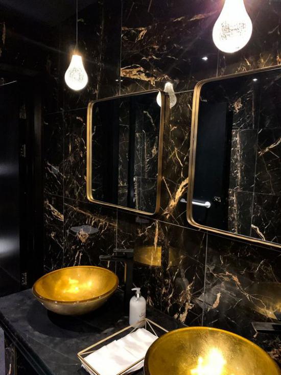 Badezimmer in Schwarz und Gold doppelter Waschtisch runde Waschbecken schwarze Marmorfliesen zwei Spiegel vergoldete Rahmen