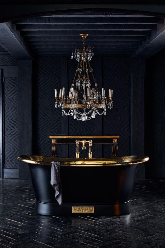 Badezimmer in Schwarz und Gold dunkles Ambiente freistehende Badewanne goldglänzende Elemente luxuriöser Kronleuchter darüber
