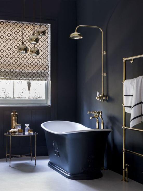 Badezimmer in Schwarz und Gold freistehende Badewanne in dunkelblau helle Armaturen Tageslicht