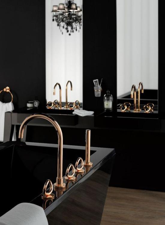 Badezimmer in Schwarz und Gold schwarze Badewanne Waschtisch Armaturen in Gold zwei Spiegel weiße Tücher
