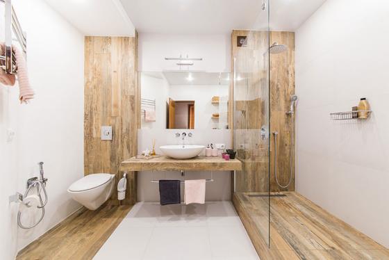 Badfliesen in Holzoptik großes Bad und WC in einem Raum symmetrisch gestaltet Duschecke mit Glaswand getrennt