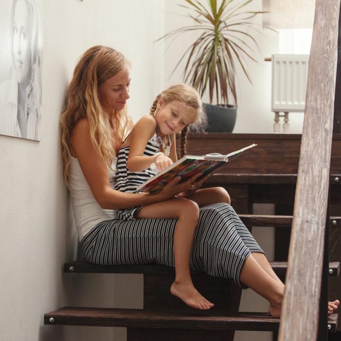 Η κρίση της Corona στο σπίτι τι κάνει η μητέρα κόρη στις σκάλες διαβάζοντας ένα παιδικό βιβλίο
