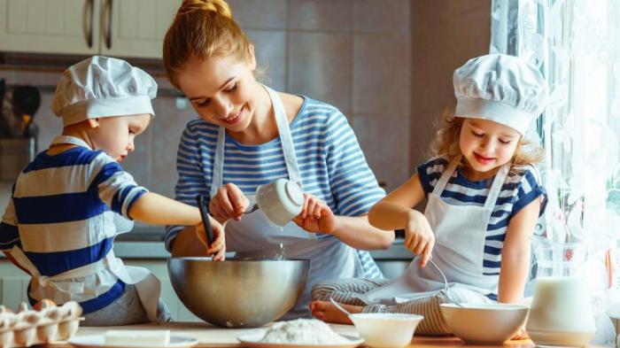 Η κρίση της Κορώνας στο σπίτι τι η μητέρα ψήνει δύο μικρά παιδιά στην κουζίνα