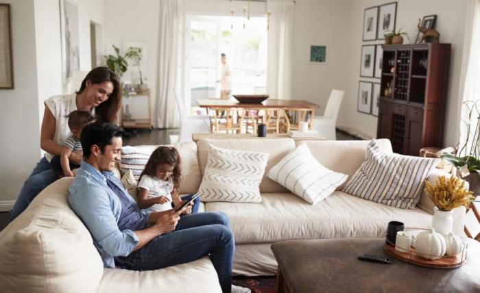 Κορώνα κρίση στο σπίτι τι οικογένεια τεσσάρων παίζουν μαζί στον καναπέ στο σαλόνι iPad