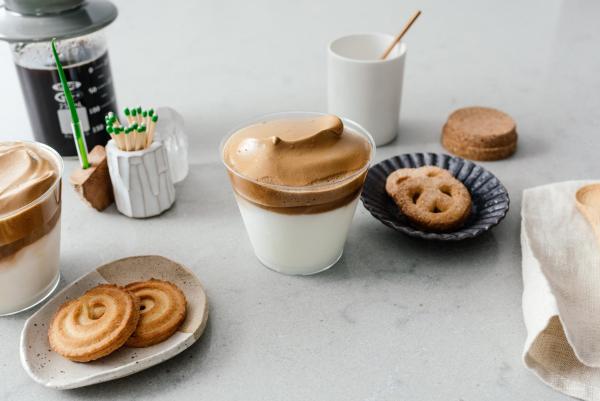 Dalgona Coffee neues trendiges Kaffeegetränk mit Kleingebäck für zwischendurch serviert