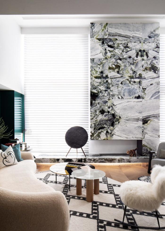 Designerwohnung in China Wohnzimmer Steinkamin bequemes geschwungenes Sofa trendige Möbel Kleiderschrank in der Ecke