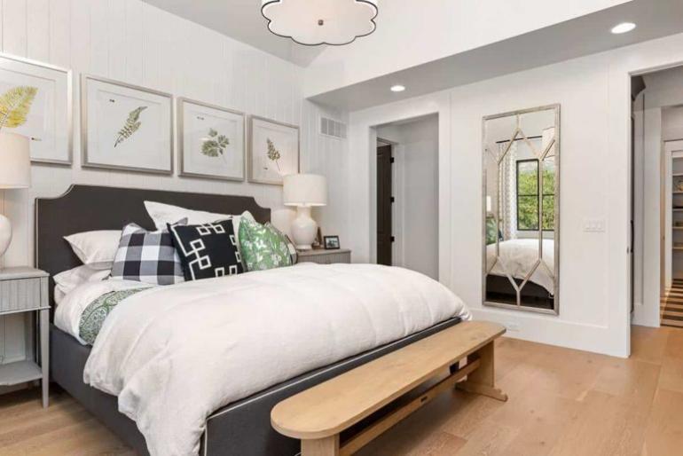 Gemütliches Bauernhaus modernes Interieur Hauptschlafzimmer einfach eingerichtet großes Schlafbett Spiegel hell und luftig