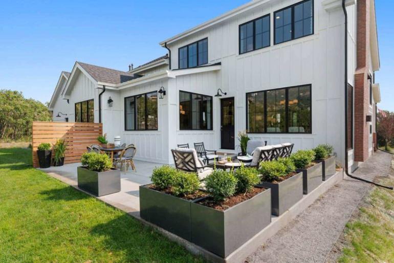 Gemütliches Bauernhaus modernes Interieur schöne Terrasse auf der Rückseite des Hauses eingerahmt von Pflanzgefäßen