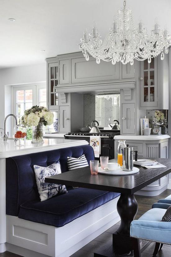 Multifunktionale Räume einen gemütlichen Sitzbereich gestalten marineblaues Sofa Esstisch schwarzer Tisch Kristallkronleuchter