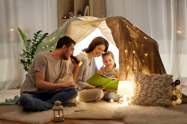 Stress vermeiden während Coronavirus Pandemie Familie zu Hause mit dem Kind spielen Zelt Bücher lesen