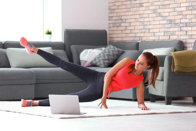 Stress vermeiden während Coronavirus Pandemie sportliche Aktivitäten zu Hause ausüben im Internet nachgucken