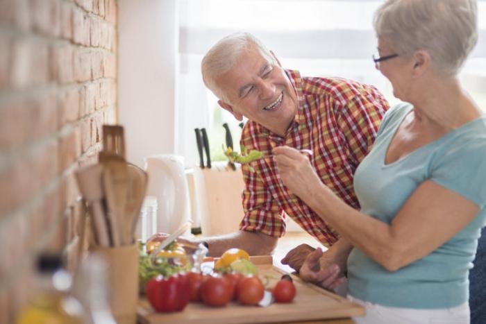 vor Coronavirus schützen zwei ältere Personen beim Kochen lachen munter sein