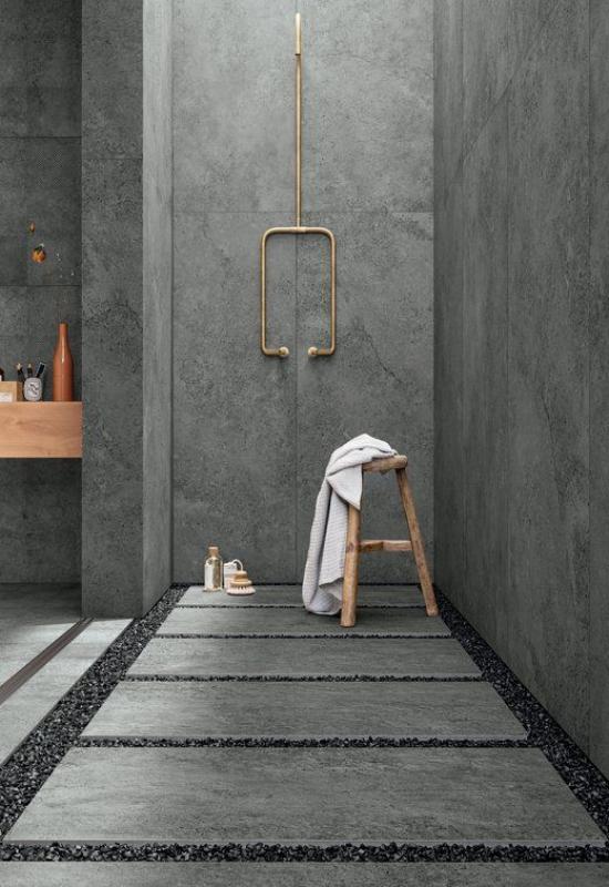 Baddesigns in Grau Industrial Style Betonwände Boden Streifen mit kleinen Steinen Dusche aus Messing