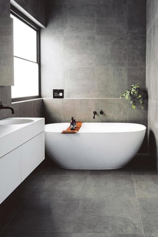 Baddesigns in Grau Minimalismus pur graue Boden-und Wandfliesen weiße Badewanne als Blickfang weißer Waschtisch Fenster rechts