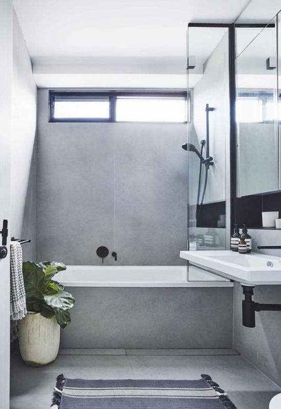 Baddesigns in Grau Ton-in-Ton Badgestaltung schwarze Badarmatur Badewannen Glaswand Spiegel