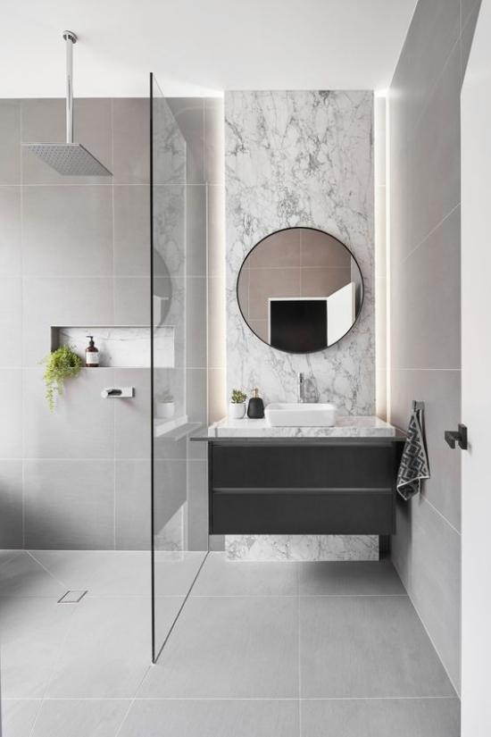 Baddesigns in Grau Waschtisch Spiegel Marmorfliesen Regendusche Glaswand eingebautes Licht