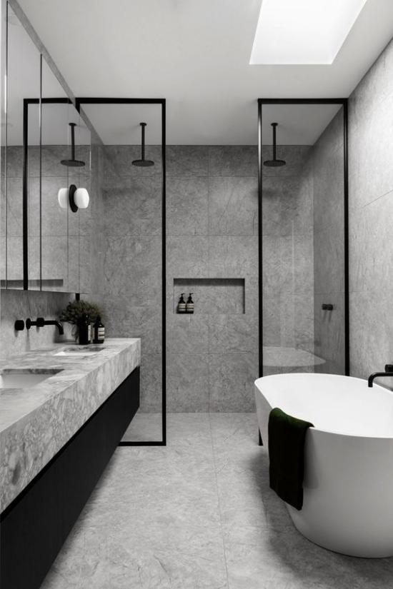 Baddesigns in Grau dominierende Farbe Grau kleine Akzente in Schwarz freistehende Badewanne weiß