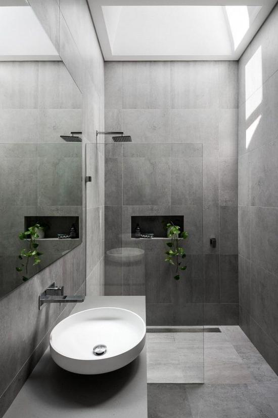 Baddesigns in Grau große Fliesen weißes rundes Waschbecken Duschecke Glaswand Tageslicht von oben grüne Badpflanze