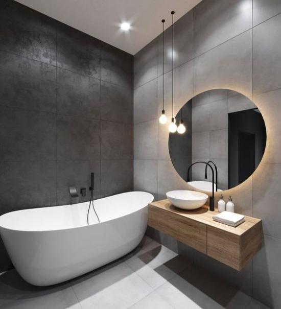 Baddesigns in Grau große graue Wandfliesenweiße Badewanne Hängelampen eingebautes Deckenlicht Waschtisch Holz runder Spiegel