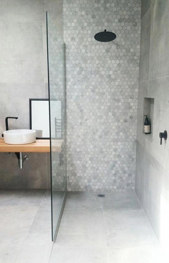 Baddesigns in Grau kleine Fliesen Duschecke Glaswand große Bodenfliesen Waschtisch Holz kleines weißes Waschbecken