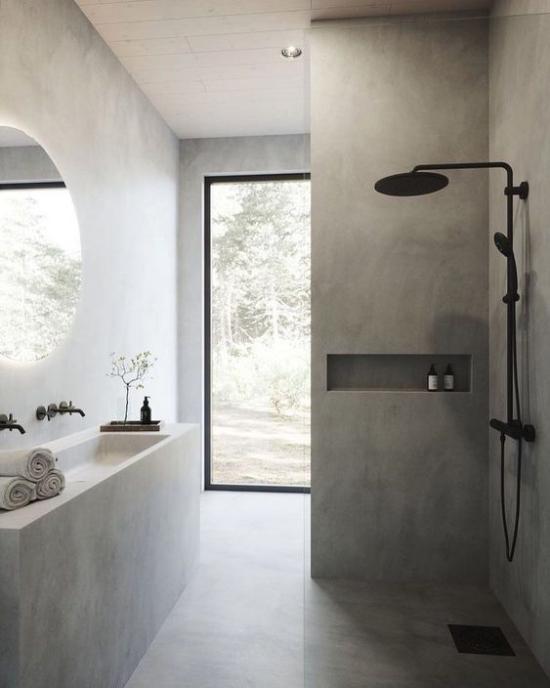 Baddesigns in Grau schönes Bad Duschecke schwarze Armatur langer Waschtisch Glastür runder Wandspiegel