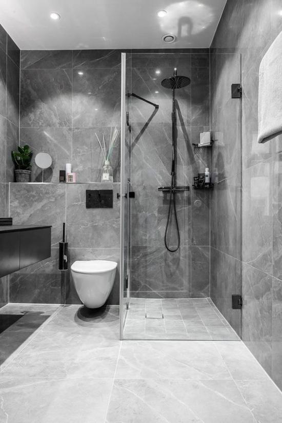 Baddesigns in Grau schönes modernes Bad graue Marmorfliesen schwarze Badarmaturen eingebautes Licht Glaswand