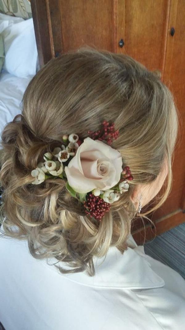 Brautfrisur mit Blumen niedriger Dutt Rose