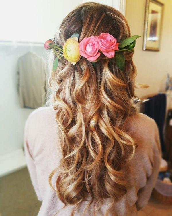 Brautfrisur mit Blumen offen romantische Wellen
