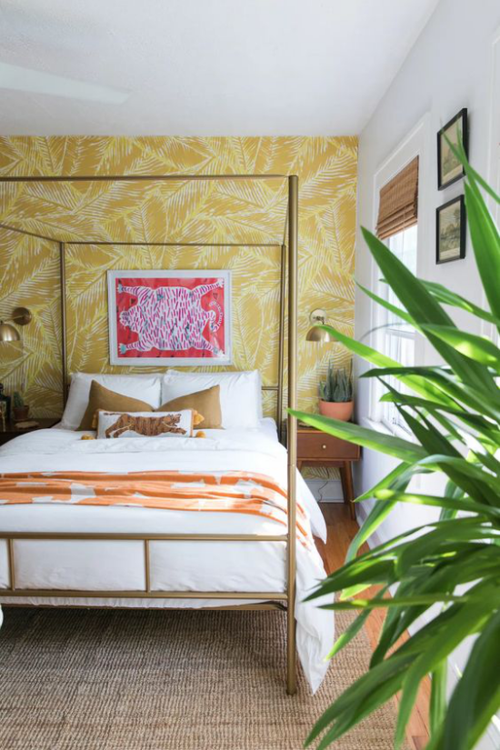 Glamouröse Schlafzimmer Himmelbett aus Metall Wand hinter dem Bett mit gelber Tapete grüne Zimmerpflanze rechts vorne