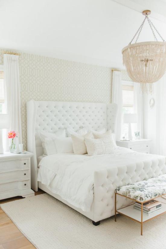 Glamouröse Schlafzimmer ganz in Weiß gestaltet gepolstertes Bett weiche Bettwäsche Deko Kissen Kronleuchter rosa Blume in Vase aus dem Nachttisch