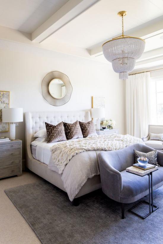 Glamouröse Schlafzimmer großes Bett runder Spiegel an der Wand Kronleuchter beigefarbene Kissen weiche Texturen