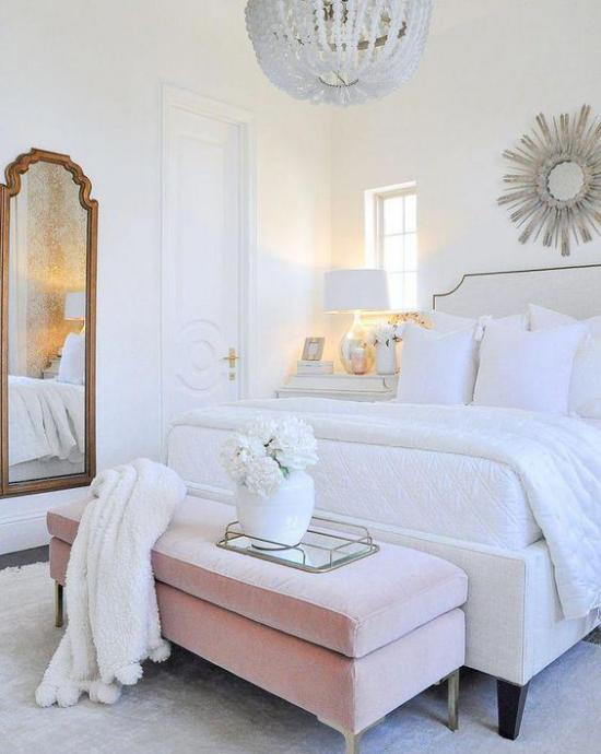 Glamouröse Schlafzimmer großes bequemes Schlafbett weiße Bettwäsche rosa Sitzbank weiße Vase mit Blumen Spiegel weiße Wurfdecken