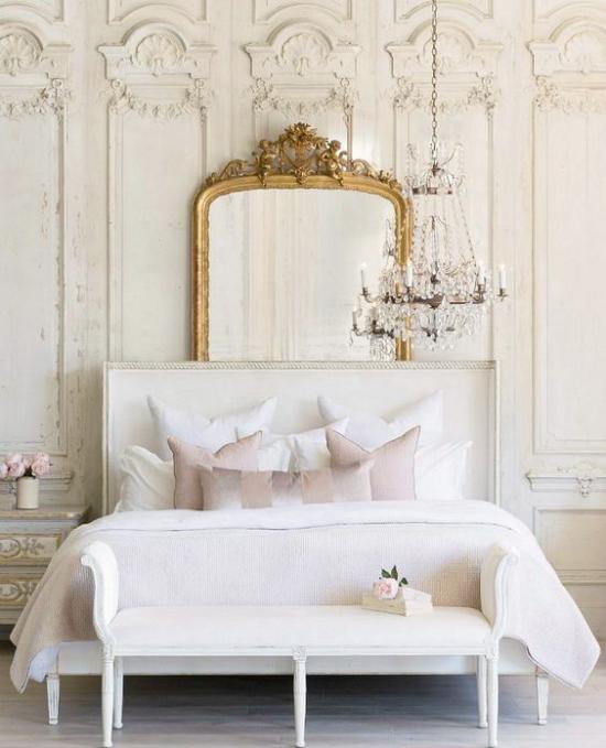 Glamouröse Schlafzimmer schickes Bett Bank weiße Bettwäsche aufwändige Wandverzierungen Retro Schmuck am Spiegel