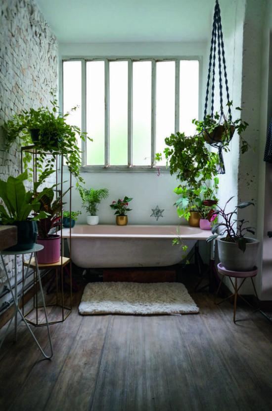 Grün im Bad Badewanne vor dem Fenster Badezimmer im rustikalen Stil viele Grünpflanzen Blumenständer Blumenampeln