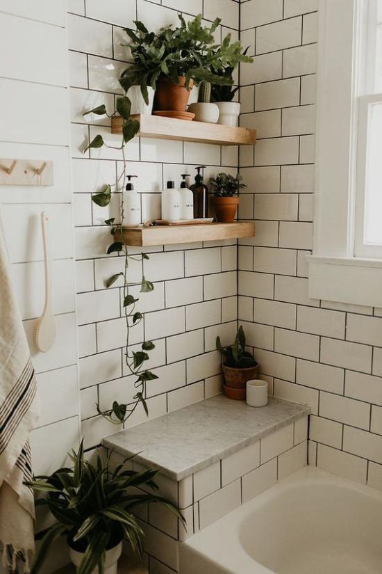 Grün im Bad Regale aus Holz an der Wand Badkosmetik Grünpflanzen weiße Fliesen Badewanne