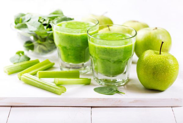 Selleriesaft Selleriestangen zwei grüne Äpfel Spinatblätter