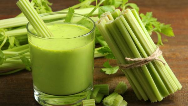 Selleriesaft ein Glas grünes Trendgetränk Selleriestangen daneben