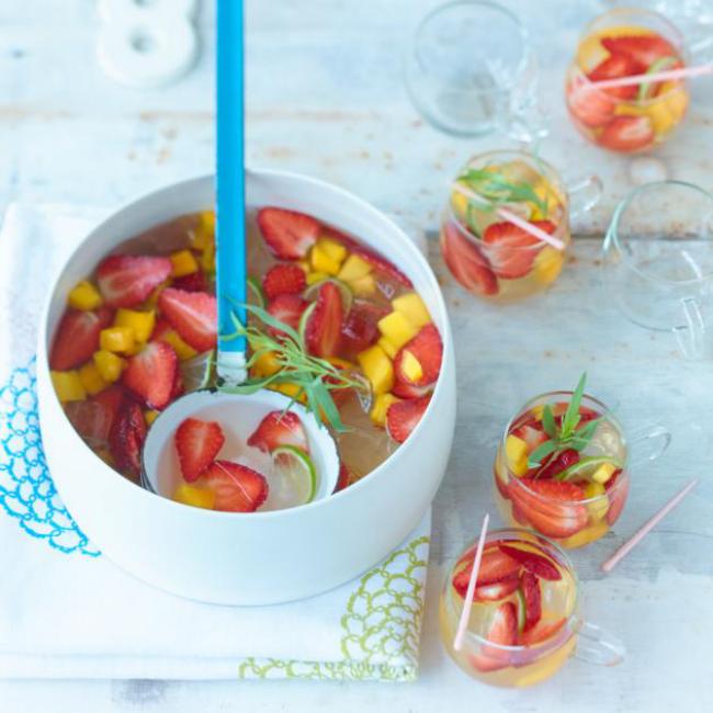 Sommerbowle zubereiten Erdbeeren Ananas in Stücke geschnitten grüne Blätter Rosmarin garnieren