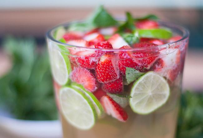 Sommerbowle zubereiten Erfrischungsgetränk an heißen Tagen ein Glas mit Erdbeeren Zitronenscheiben Minze