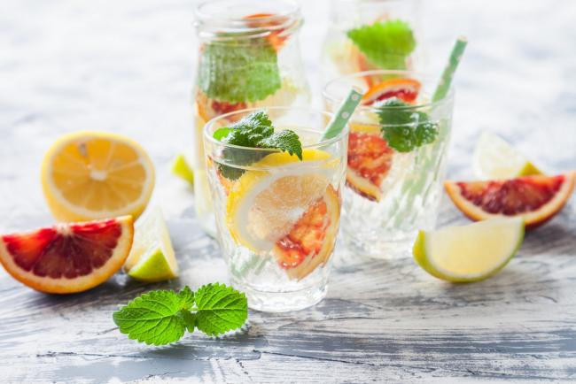 Sommerbowle zubereiten frisch lecker Zitrone in Scheiben geschnitten Minze Blätter im Glas