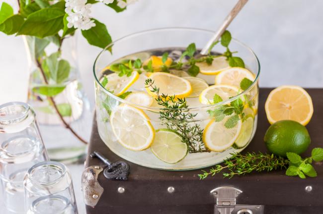 Sommerbowle zubereiten frisch lecker Zitrone in Scheiben schneiden auf einem Holzbrett