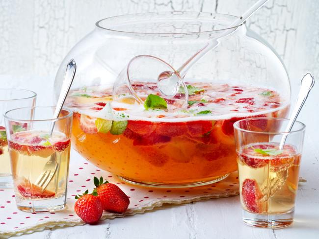 Sommerbowle zubereiten frisch lecker fruchtig Erdbeeren Saft Blätter frische Minze in Glasschale Gläser