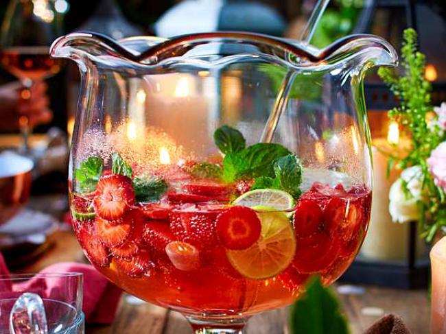 Sommerbowle zubereiten frisch lecker fruchtig Erdbeeren Saft Blätter frische Minze in Glasschale zwei Gläser