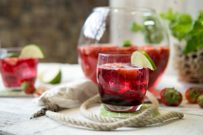 Sommerbowle zubereiten frisch lecker fruchtig Erdbeeren Zitronenscheiben Eiswürfel im Glas