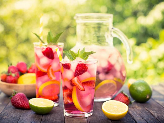 Sommerbowle zubereiten frisch lecker fruchtig Erdbeeren Zitronenscheiben große Glaskanne in Gläsern serviert
