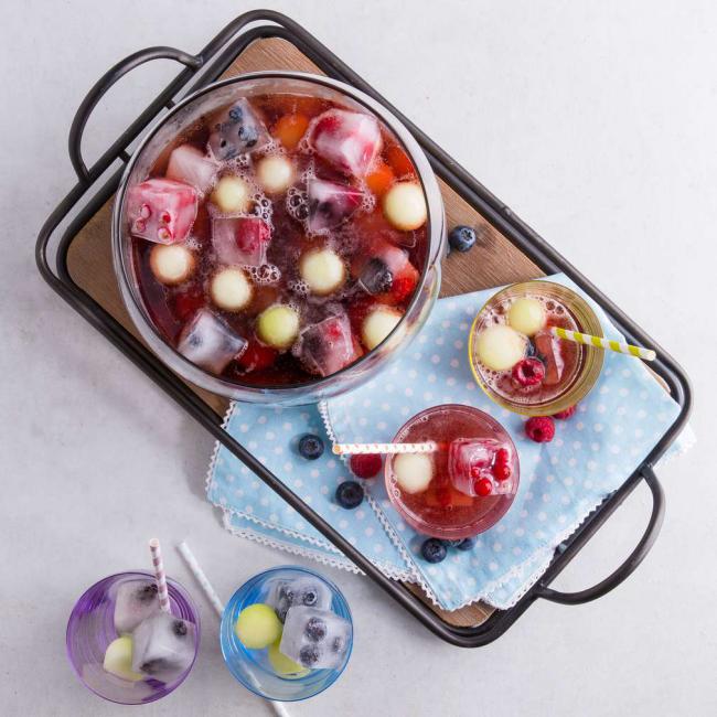 Sommerbowle zubereiten frisch lecker fruchtig Früchte Himbeeren Brombeeren in Eisformen eingefroren
